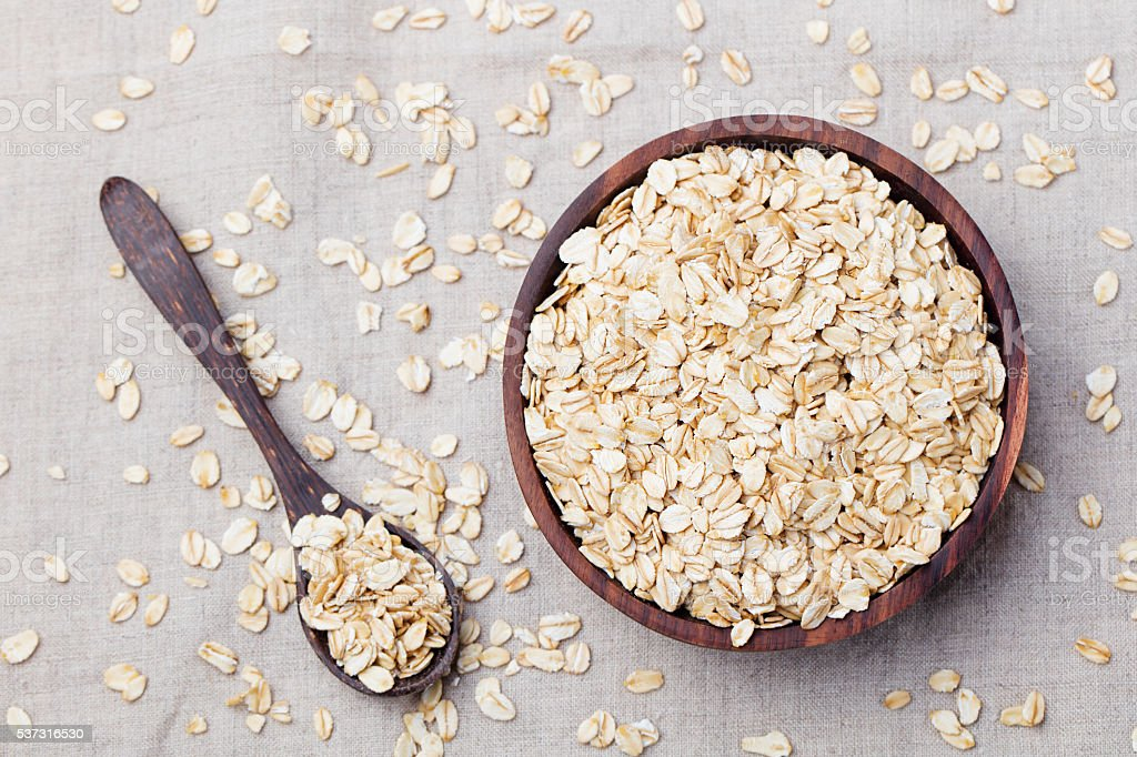Healthy breakfast Organic oat flakes in a wooden bowl stock photo