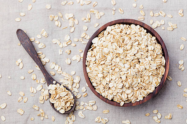 Healthy breakfast Organic oat flakes in a wooden bowl Healthy breakfast Organic oat flakes in a wooden bowl Grey textile background Top view Copy space oatmeal stock pictures, royalty-free photos & images
