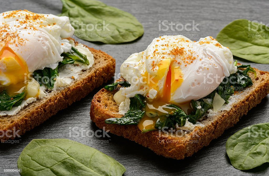 Healthy breakfast, sandwich with creme cheese, spinach and poached egg. stock photo