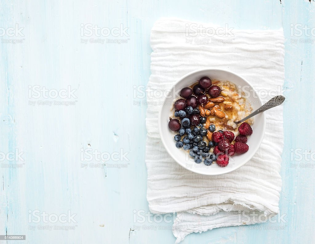 Healthy breakfast set. Bowl of oat porridge with fresh berries stock photo