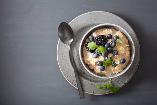 healthy breakfast steel cut oatmeal porridge with blueberry blackberry - porridge foto e immagini stock