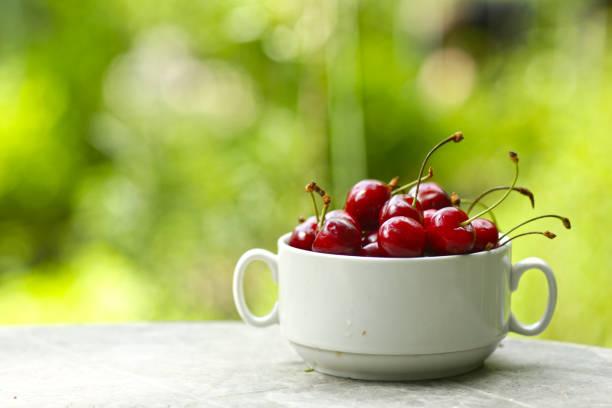 healthy breakfast - sweet cherry in bowl close up photo on green grass background - salud zdjęcia i obrazy z banku zdjęć