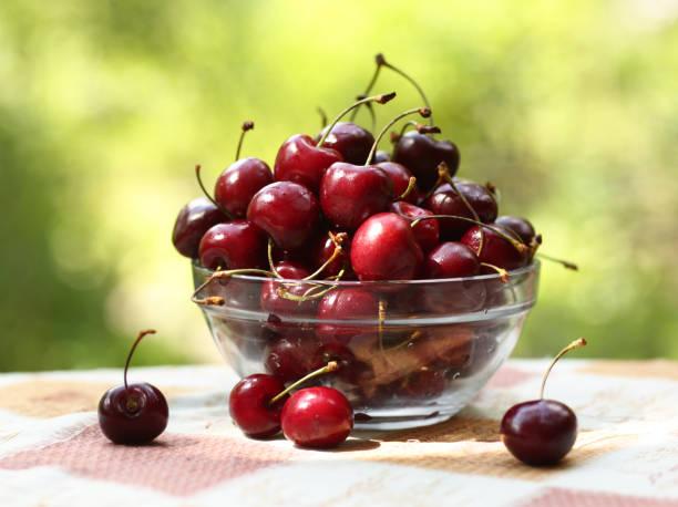 건강한 아침 식사 - 그릇에 달콤한 체리 녹색 잔디 배경에 사진을 닫습니다 - salud 뉴스 사진 이미지