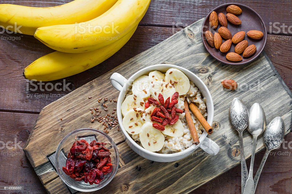 Healthy breakfast table: oat porridge, fruits and nuts stock photo