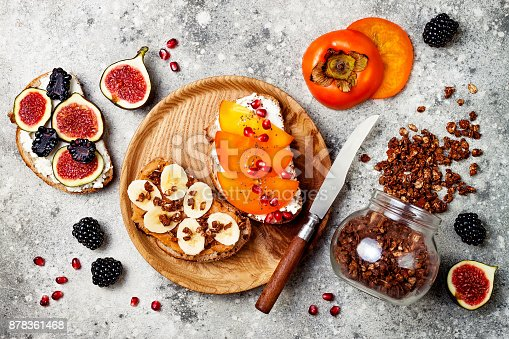 Healthy breakfast toasts with peanut butter, banana, chocolate granola, cream cheese, figs, blackberry, persimmon, pomegranate, chia seeds. Top view, overhead