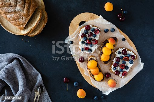 Healthy breakfast toasts with ricotta cheese, blueberries, apricots, sweet cherry. Top view, overhead on black background