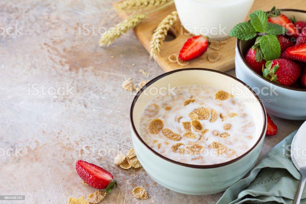 Healthy breakfast - whole grain flakes, milk and fresh strawberries on stone or slate background. The concept of nutrition health. Copy space. - Zbiór zdjęć royalty-free (Bez ludzi)