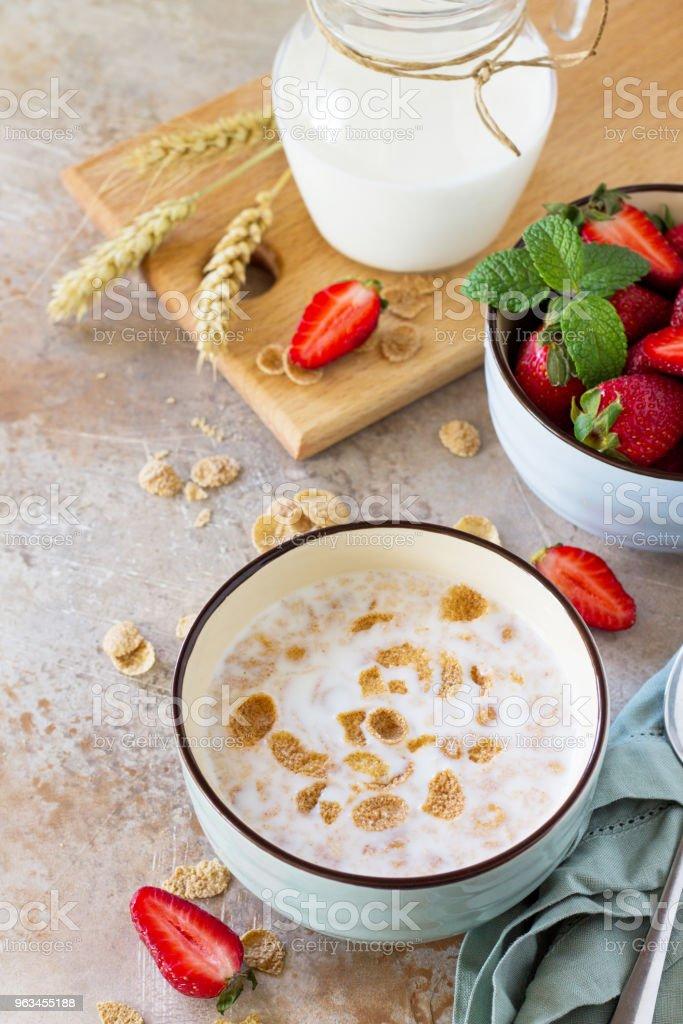 Hälsosam frukost - hela korn flingor, mjölk och färska jordgubbar på sten eller skiffer bakgrund. Begreppet hälsa. - Royaltyfri Bildbakgrund Bildbanksbilder