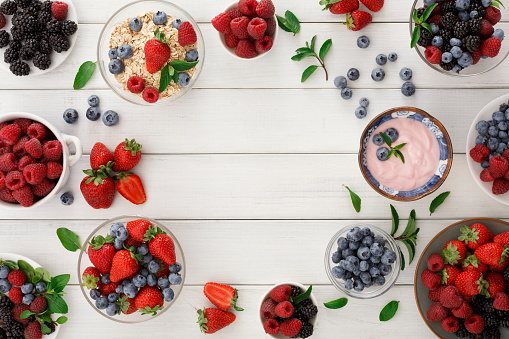 istock Healthy breakfast with berries and yogurt on white wooden table 863559880