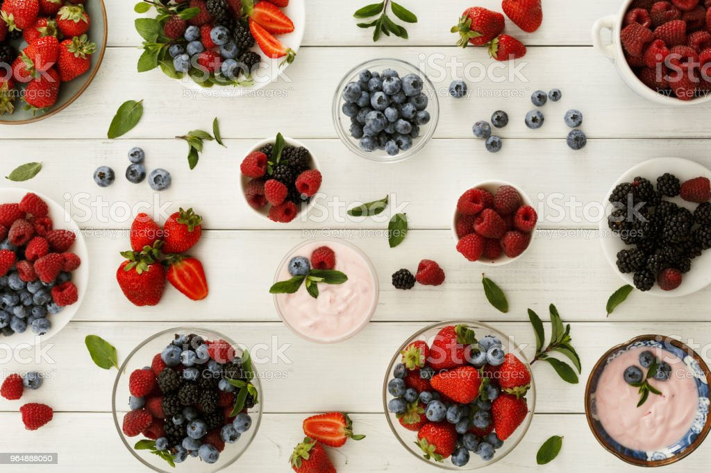 Healthy breakfast with berries and yogurt on white wooden table royalty-free stock photo