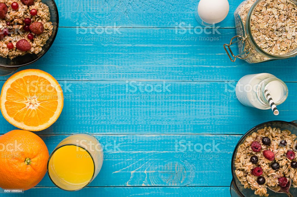 healthy breakfast with bowl of homemade oatmeal with berries and orange juice over rustic wooden background stock photo