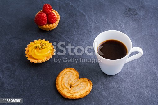 cofee, berries, croissant and French pastryon black stone background, studio shot