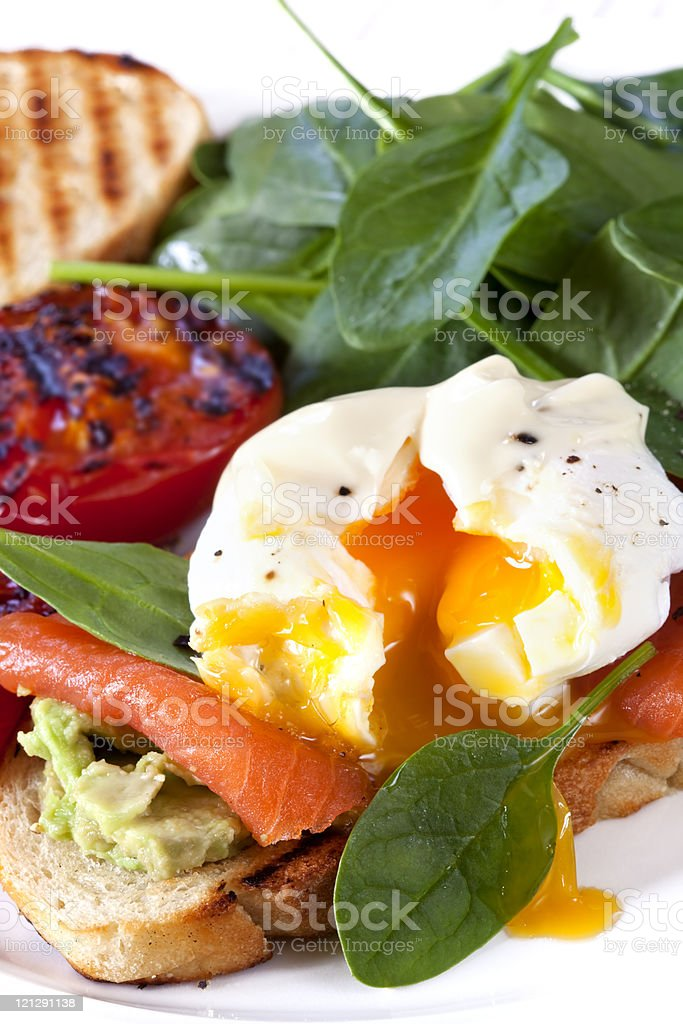 Healthy breakfast with egg, spinach, salmon and avocado stock photo