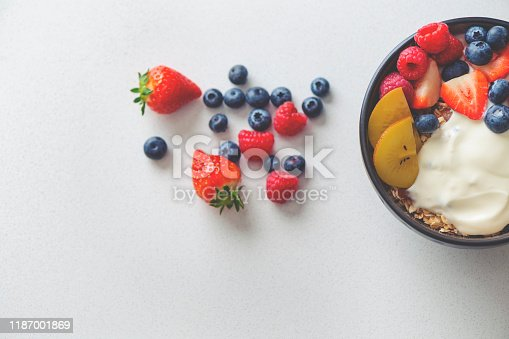Healthy breakfast with fruit. It includes strawberries, blueberries, kiwifruit, granola and yoghurt. High angle with copy sapce