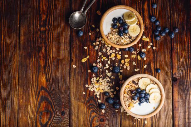 gesundes frühstück mit müsli, bananen und heidelbeere. - haferflocken rosinen stock-fotos und bilder