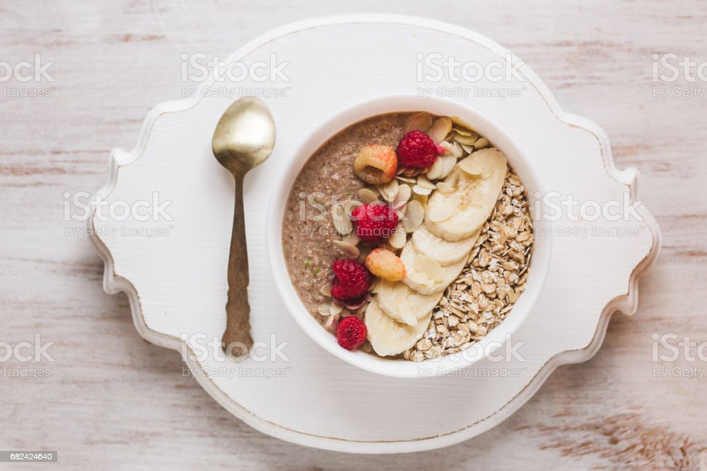Healthy breakfast with granola, berries, nuts and smoothie. Isolated on white textured wooden background royalty-free stock photo