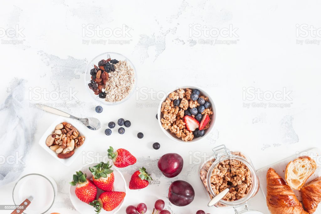 Healthy breakfast with muesli, fruits, berries, nuts on white background stock photo