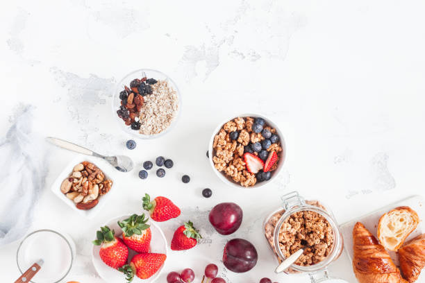 healthy breakfast with muesli, fruits, berries, nuts on white background - oats food stock photos and pictures