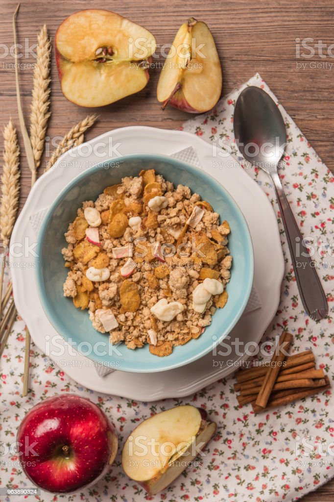 Healthy breakfast with muesli, red apple and cinnamon on rustic wooden table. Top view with copy space. - Royalty-free Apple - Fruit Stock Photo