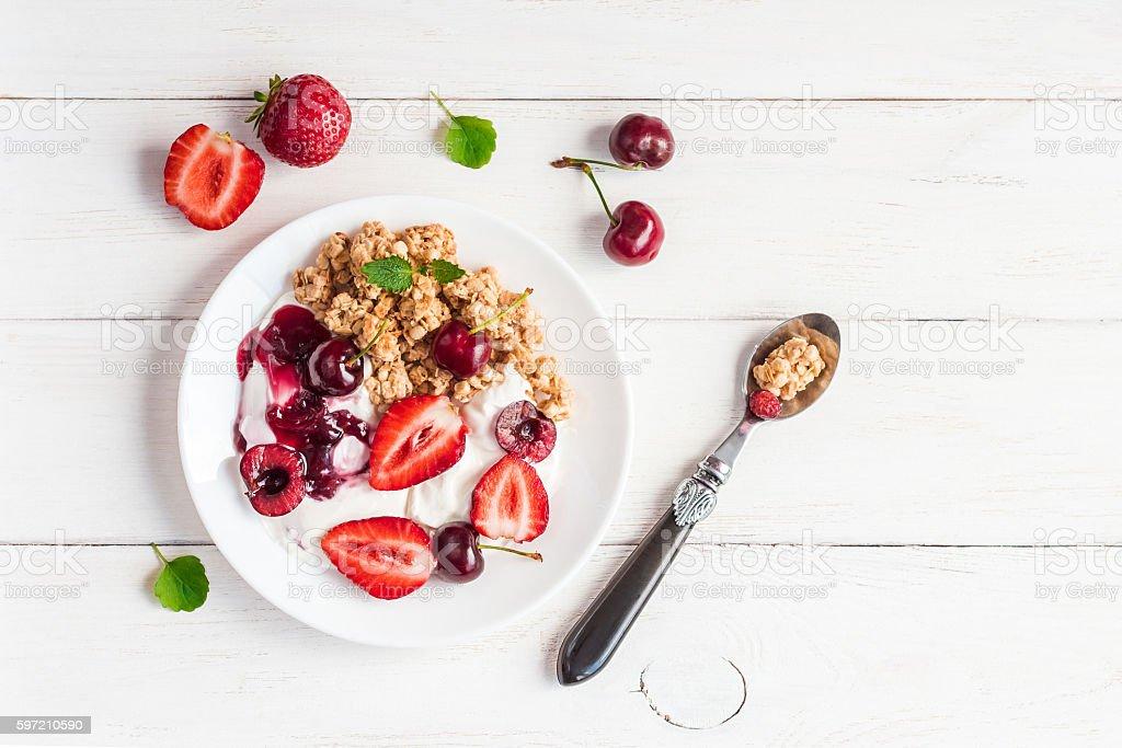 healthy breakfast with yogurt, muesli and berries, flat lay stock photo