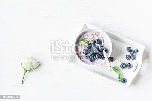 istock Healthy breakfast with yogurt, muesli and blueberry. Flat lay 599887760
