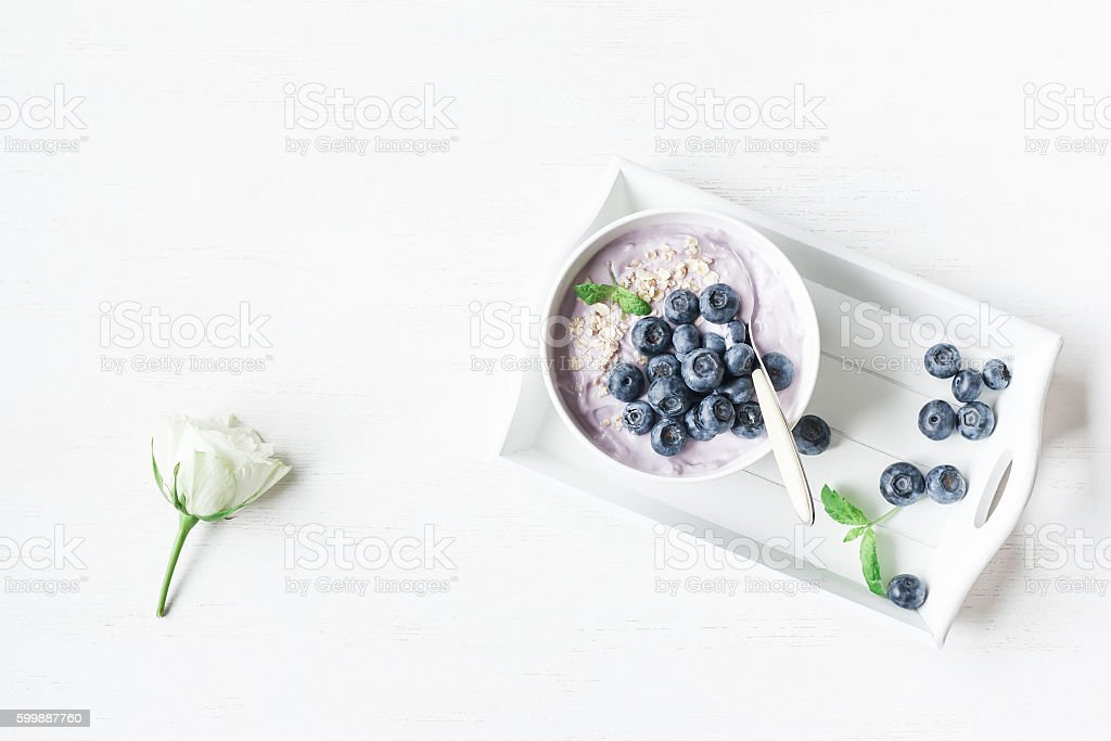 Healthy breakfast with yogurt, muesli and blueberry. Flat lay stock photo