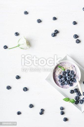 599887760 istock photo Healthy breakfast with yogurt, muesli and blueberry. Flat lay 599888018