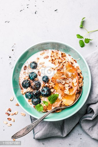 825171518 istock photo Healthy breakfast - yoghurt, oat flakes, blueberries and apples 1152371331