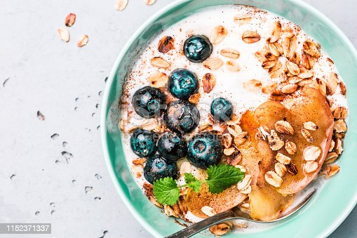 825171518 istock photo Healthy breakfast - yoghurt, oat flakes, blueberries and apples 1152371337