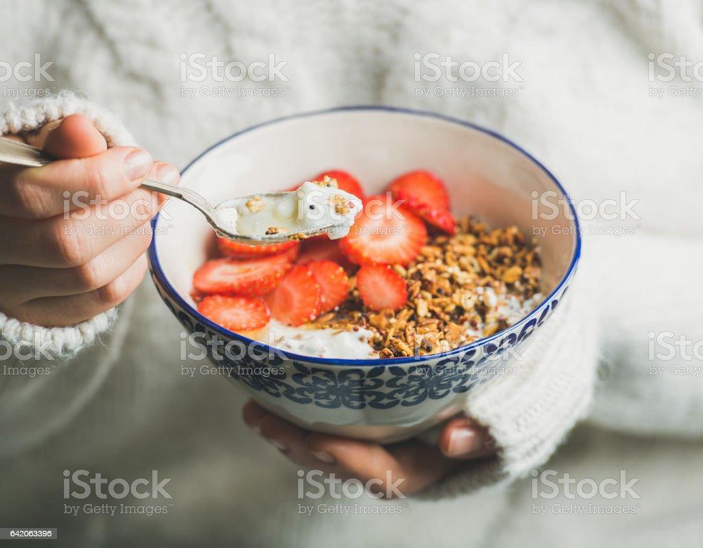 Healthy breakfast yogurt, granola, strawberry bowl in woman's hands stock photo