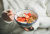 Healthy breakfast yogurt, granola, strawberry bowl in woman's hands
