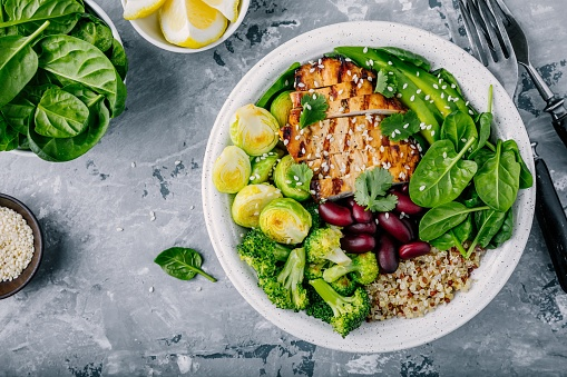 istock Healthy buddha bowl lunch with grilled chicken, quinoa, spinach, avocado, brussels sprouts, broccoli, red beans with sesame seeds 920931456