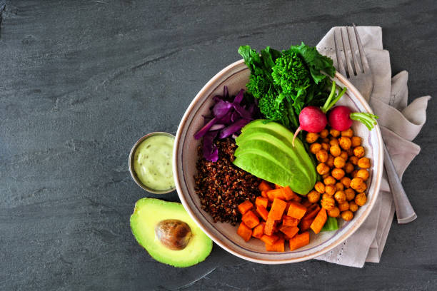 Healthy Buddha bowl with rapini, quinoa, sweet potato, chickpeas and avocado, top view scene over dark slate stock photo