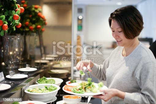 A Chinese ethnicity female adult is selecting fresh fruit and vegetable salad for breakfast.