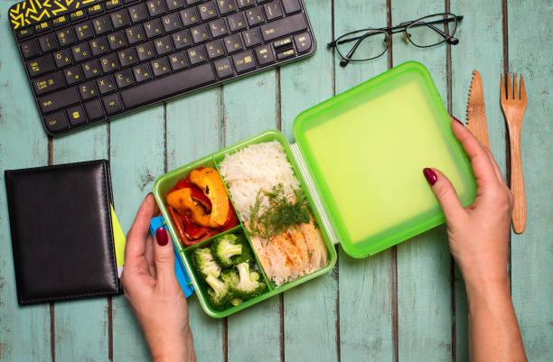 Gesundes Business-Lunch am Arbeitsplatz. Gesundes Lebensmittelkonzept – Lunchbox mit Huhn, Reis, Brokkoli und gegrillter Paprika auf dem Schreibtisch mit Laptop-Notebook und Brille. – Foto