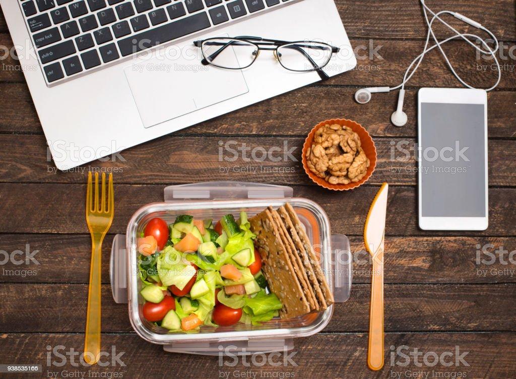 Friska affärslunch på arbetsplatsen. Sallad, lax, avokado och nötter lunch låda på skrivbord med laptop, smartphone, Glasögon och hörlurar. - Royaltyfri Affärsman Bildbanksbilder
