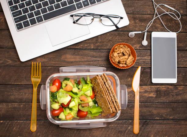 Gesunden Business-Lunch am Arbeitsplatz. Salat, Lachs, Avocado und Nüssen lunch Box auf Schreibtisch mit Laptop, Smartphone, Brille und Kopfhörer. – Foto