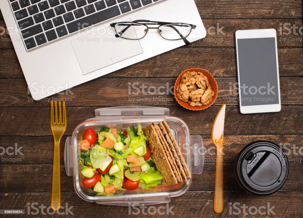Friska affärslunch på arbetsplatsen. Sallad, lax, avokado och nötter lunch låda på skrivbord med laptop, smartphone, Glasögon och kaffe. - Royaltyfri Affärsman Bildbanksbilder