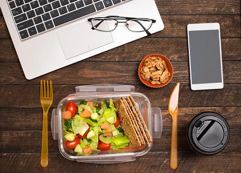 Friska Affärslunch På Arbetsplatsen Sallad Lax Avokado Och Nötter Lunch Låda På Skrivbord Med Laptop Smartphone Glasögon Och Kaffe-foton och fler bilder på Affärsman