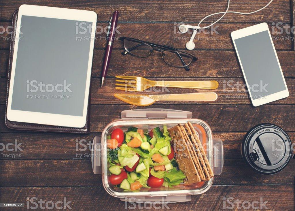 Friska affärslunch på arbetsplatsen. Sallad, lax, avokado matlåda på skrivbord med surfplatta, smartphone, Glasögon och hörlurar. - Royaltyfri Affärsman Bildbanksbilder
