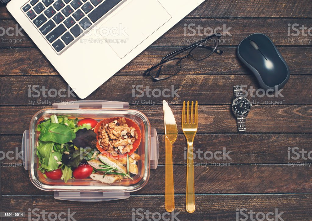 Healthy business lunch at workplace. Vegetables and fried chicken lunch box on working desk with laptop watches and glasses. stock photo