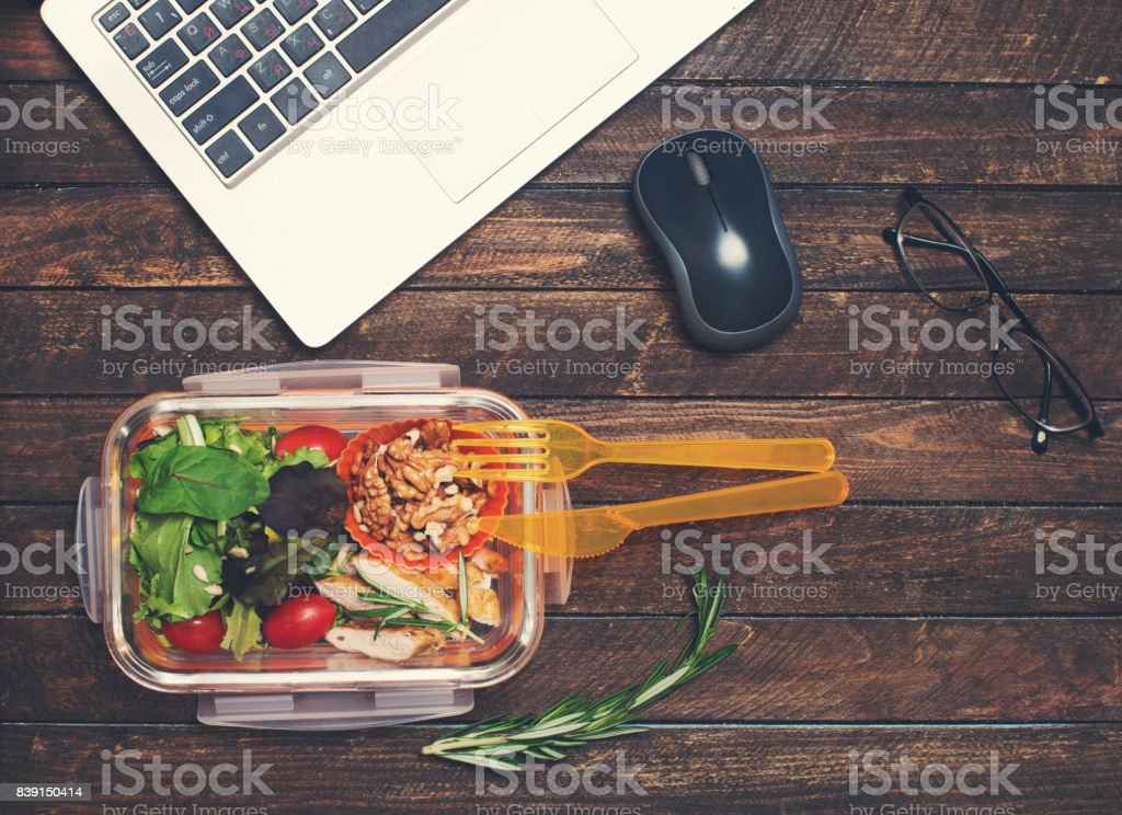 Healthy business lunch at workplace. Vegetables and fried chicken lunch box on working desk with laptop and glasses. stock photo