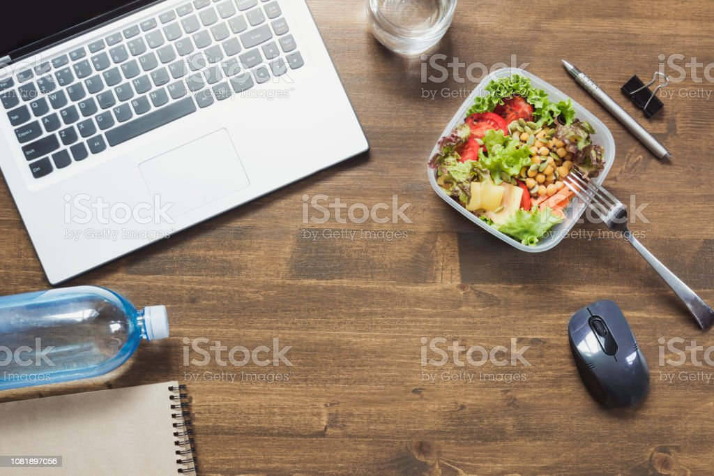 Healthy business lunch in office, salad, water on wooden table. Top...