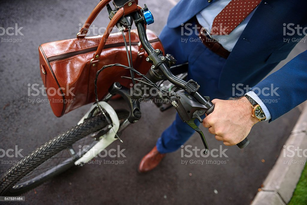 Healthy businessman cycling with bag stock photo