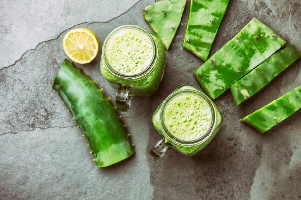 friska cactus nopales, aloe vera och citron detox drink i burkar och ingredienser på grå bakgrund. ovanifrån - cactus lime bildbanksfoton och bilder