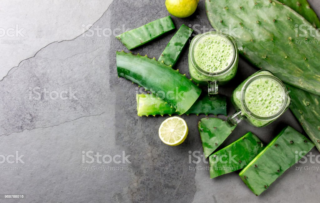 Healthy cactus nopales, aloe vera and lemon detox drink in jars and ingredients on gray background. Top view stock photo