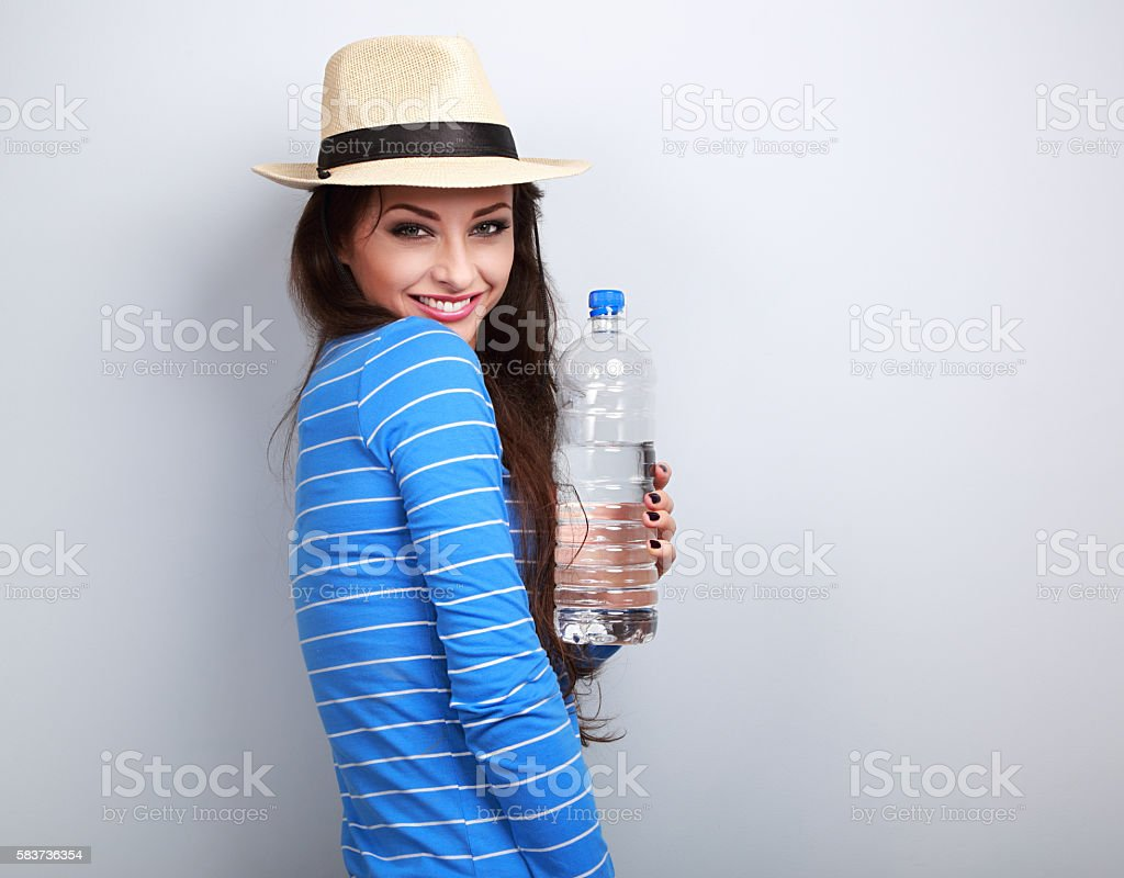 Healthy casual woman in summer hat holding bottle of water stock photo