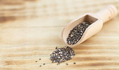 Healthy chia seeds in wooden spoon on wood table close-up. Space for your text