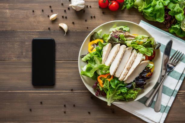 salada de frango saudável ao lado de smartphone em fundo de tabela de madeira - porção de comida - fotografias e filmes do acervo