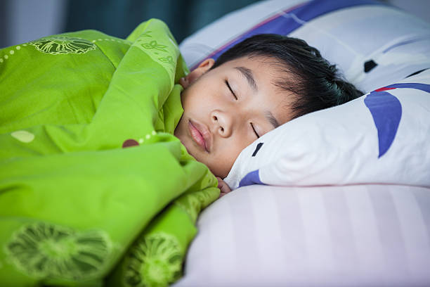 Healthy child. Little asian boy sleeping peacefully on bed. stock photo
